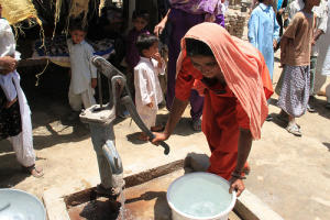 Woman getting water from a pump in Pakistan
