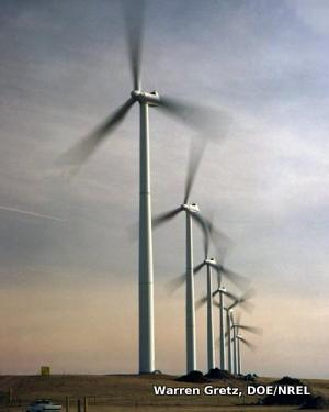 ... wind turbines in a wind farm with a truck in the foreground for scale