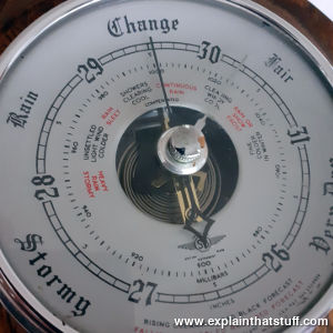 A wooden aneroid barometer with weather forecasting descriptions marked on its dial.