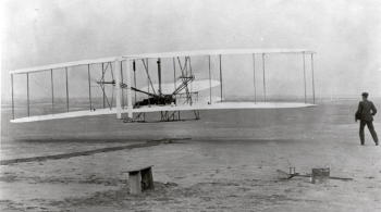 The Wright brothers flying the first engine-powered plane at Kitty Hawk in 1903
