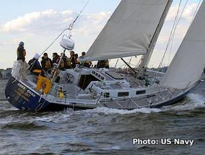 A racing yacht tipped over by the wind is balanced by sailors sitting along the side.
