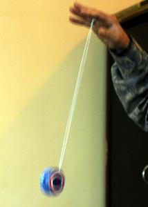 A blue yoyo rolls up and down its string.